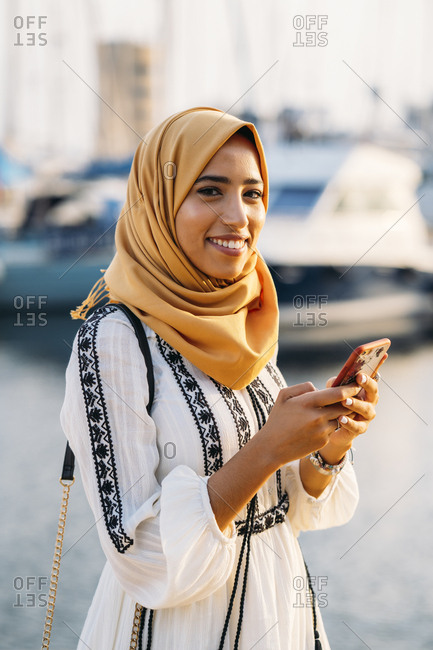 Young Muslim woman wearing yellow hijab walking at the harbor