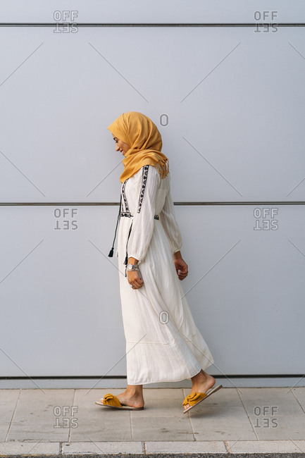 Young Muslim woman wearing yellow hijab and walking in front of a white wall