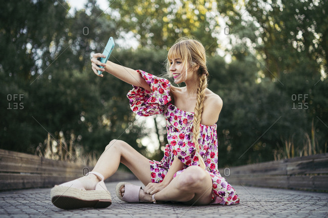 Portrait of smiling young woman  sitting on boardwalk in summer taking selfie with smartphone