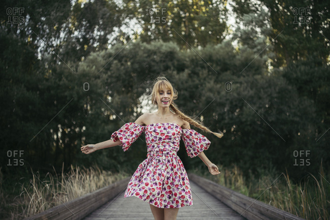 Portrait of happy young woman wearing summer dress with floral design dancing on boardwalk