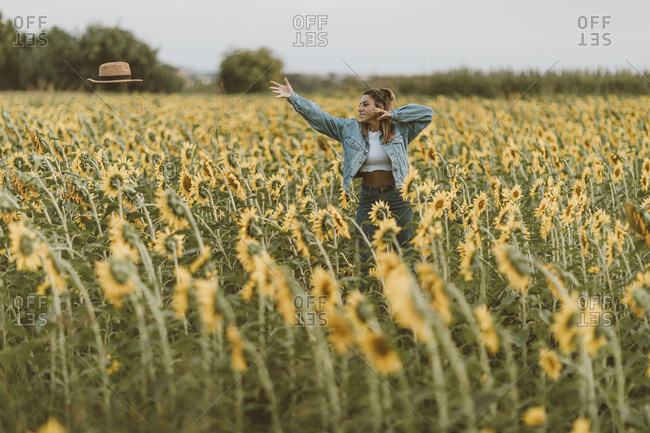 Young woman with blue denim jacket throwing a hat in a field of sunflowers