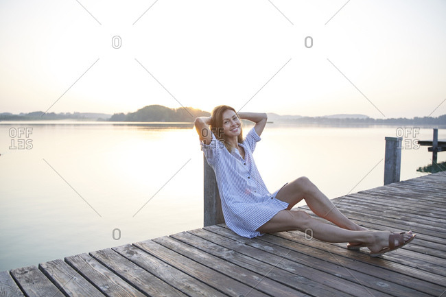 Portrait of mature woman sitting on jetty at a lake at sunrise
