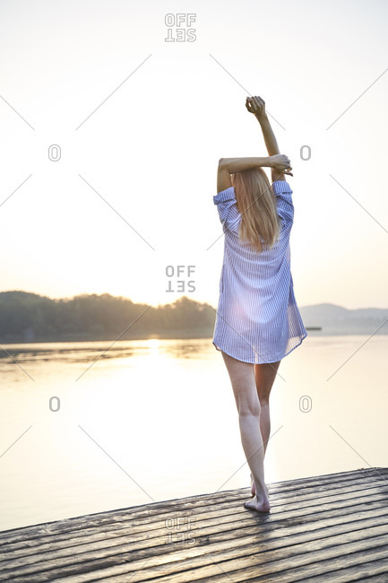 Rear view of mature woman standing on jetty at a lake at sunrise