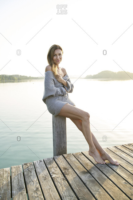 Portrait of mature woman on jetty sitting on pole at a lake