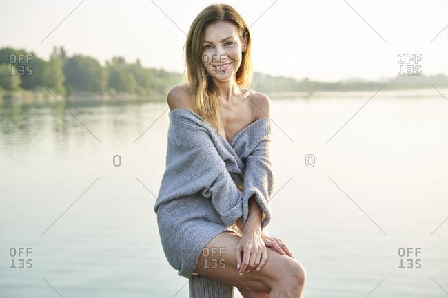 Portrait of mature woman sitting on pole at a lake