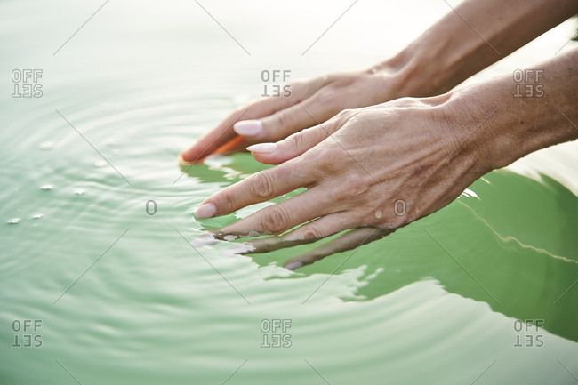 Close-up of woman's hands touching water of a lake
