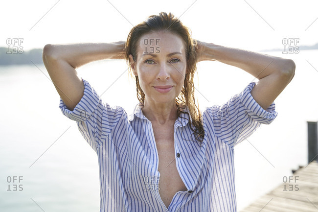 Portrait of mature woman with wet hair on jetty at a lake