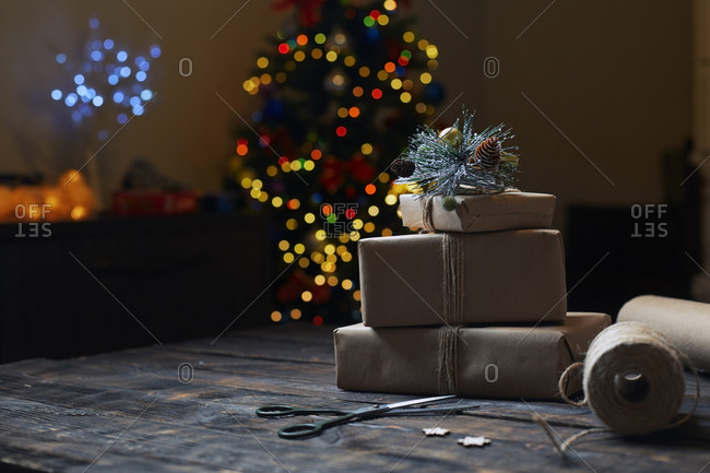 Christmas gift boxes and rope on a wooden table against the Xmas tree