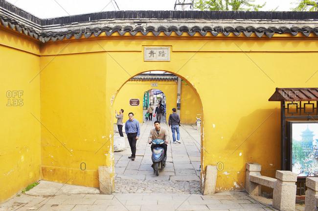 Shanghai, China - April 9, 2014: Man on motorbike riding through yellow arch