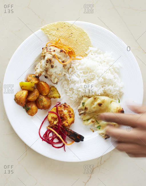 Hand reaching for food on a plate