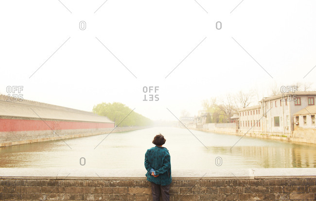 Rear view of woman looking out at river from bridge, Beijing, China