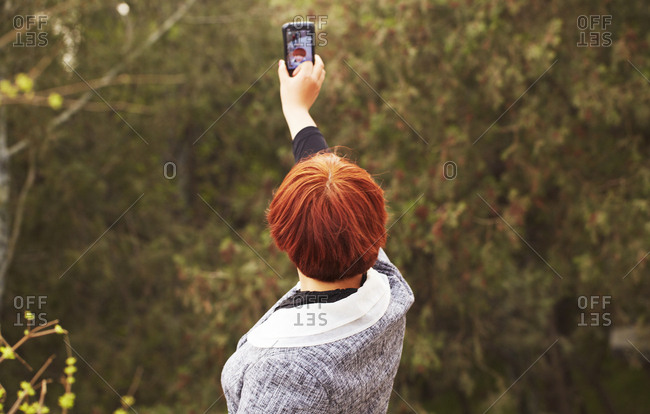 Red headed woman holding cell phone in the air taking a selfie