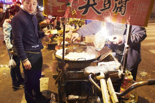 Shanghai, China - April 6, 2014: Man getting street food at night