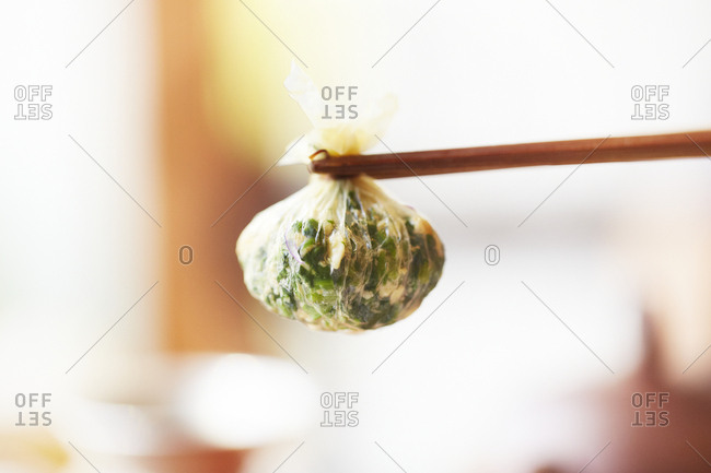 Close up of a Chinese appetizer held with chopsticks