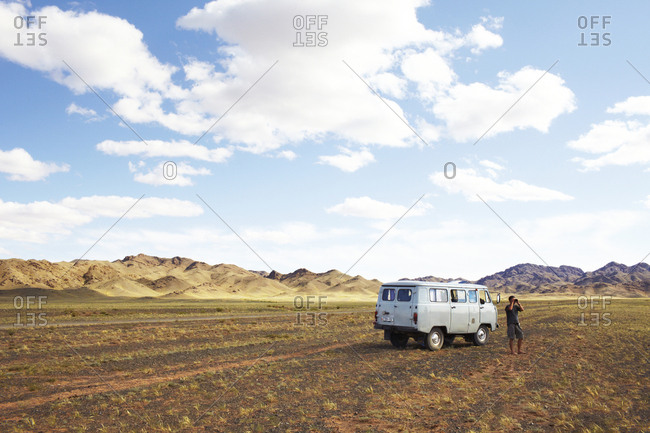 Mongolia - July 25, 2011: Man standing by campervan looking into the distance with binoculars