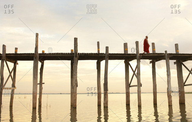 Mandalay, Myanmar - August 16, 2009: Buddhist monk walking across U Bein Bridge