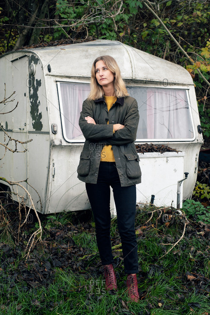 Blonde woman standing in front of old camper looking away