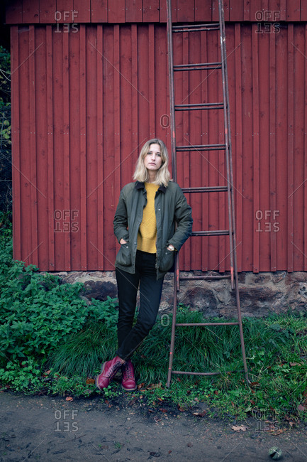Blonde woman leaning on ladder that is propped on a red barn
