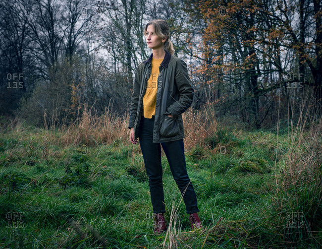 Portrait of a blonde woman standing in a forest with hand in her pocket