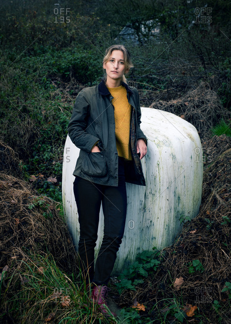 Portrait of a blonde woman in a forest with hand in her pocket
