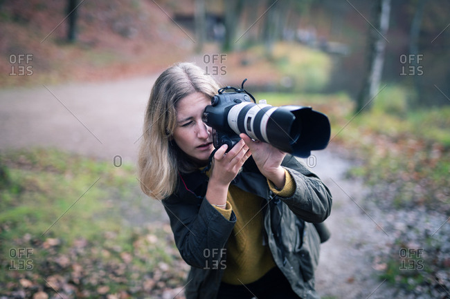 Blonde photographer using camera with large telephoto lens while taking shots in nature