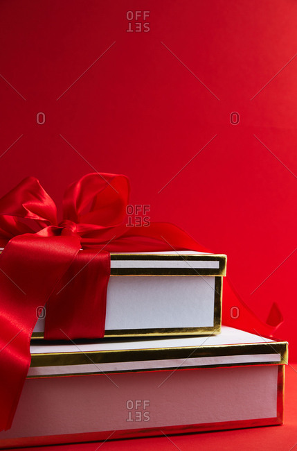 Gold and white gift boxes with red ribbon