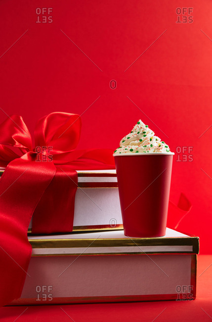 Hot beverage in a red cup on top of gift boxes with red ribbon