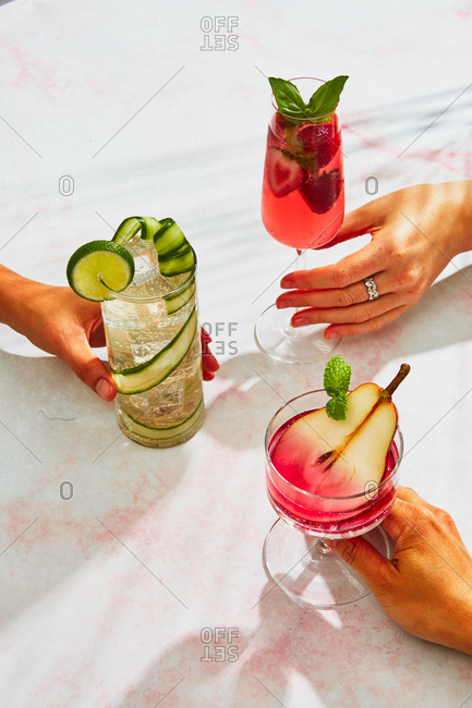 Three hands holding various cocktails