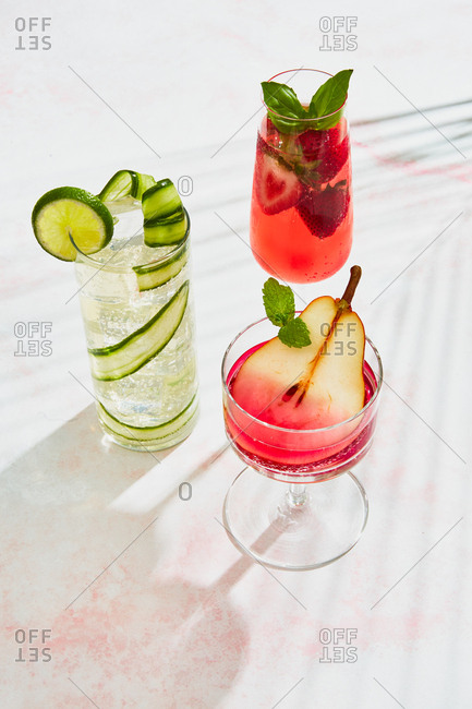 Overhead view of three fruit garnished cocktails on light marble surface