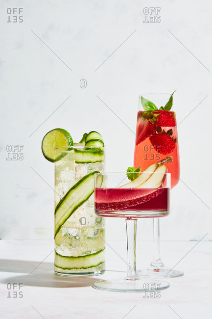 Three fruit garnished cocktails on light marble surface