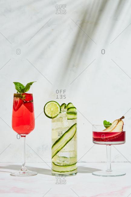 Three fruit garnished cocktails on light marble surface arranged tallest to shortest
