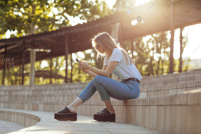 Young girl sitting in a park using her mobile phone