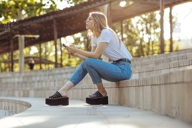 Young blonde girl sitting in a park using her mobile phone