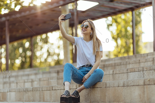 Blonde girl sitting in a park using her mobile phone to take a selfie