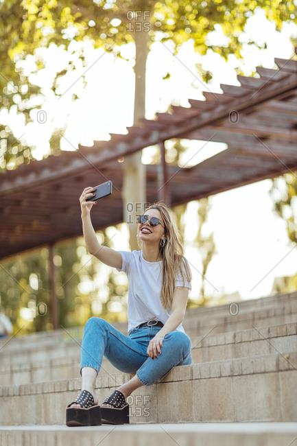 Young girl sitting in a park using her mobile phone to take a selfie