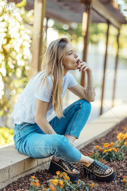 Beautiful woman sitting in a park smoking a cigarette during sunset