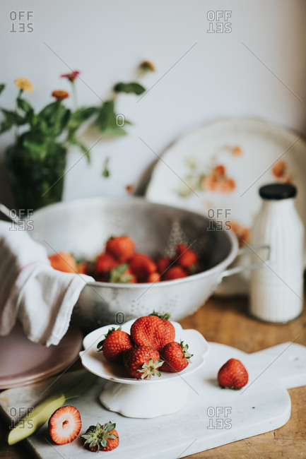 Strawberries being cut up with cleaned berries and flowers in the background