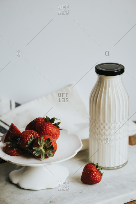 Bottle of cream with strawberries sitting in front of it.
