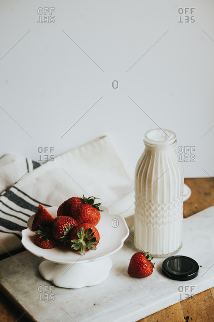 Strawberries on a stand with a bottle of cream and a spoon
