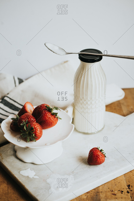 Bottle of cream with spoon balanced on top with a mini stand of strawberries