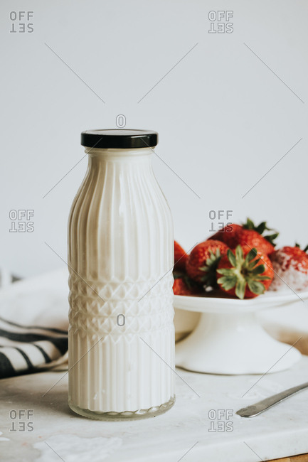 Vintage jar of cream with strawberries in the background