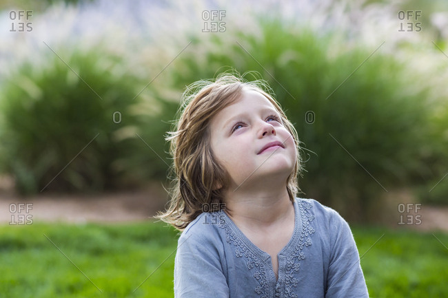 5 year old boy relaxing on lush green lawn looking up