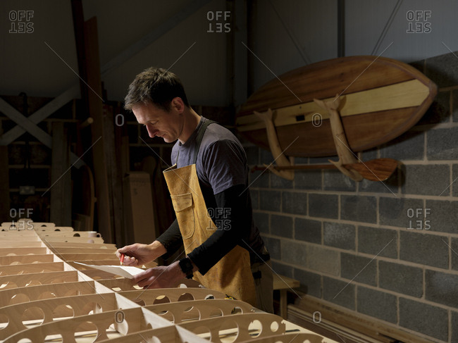 Man at work standing over wooden paddleboard in workshop holding paper and pencil