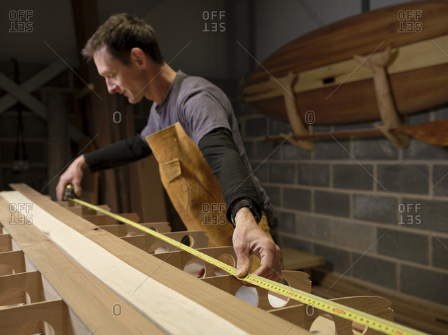 Man in workshop using expanding tape measure to make wooden paddleboard