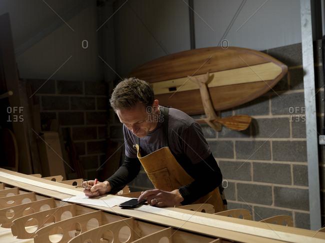 Paddleboard maker using digital device in workshop