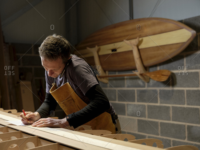 Paddleboard maker using mobile phone in workshop