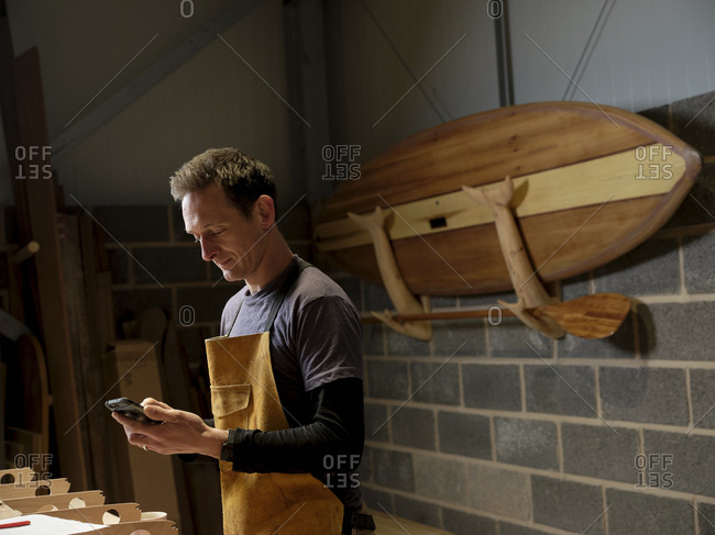 Paddleboard maker using mobile device in workshop