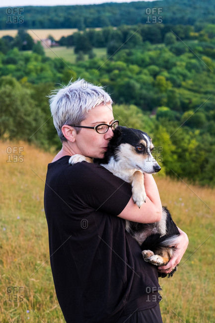 Woman with short grey hair wearing glasses standing on a hillside, holding dog.