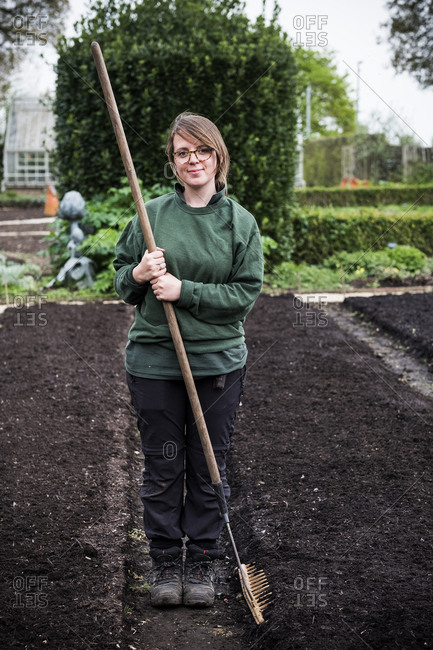 Smiling woman holding wooden rake standing on a freshly laid bed of soil in a vegetable garden.