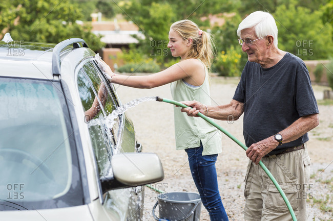 Senior man, grandfather and his 13 year old grand daughter washing a car  together in driveway stock photo - OFFSET